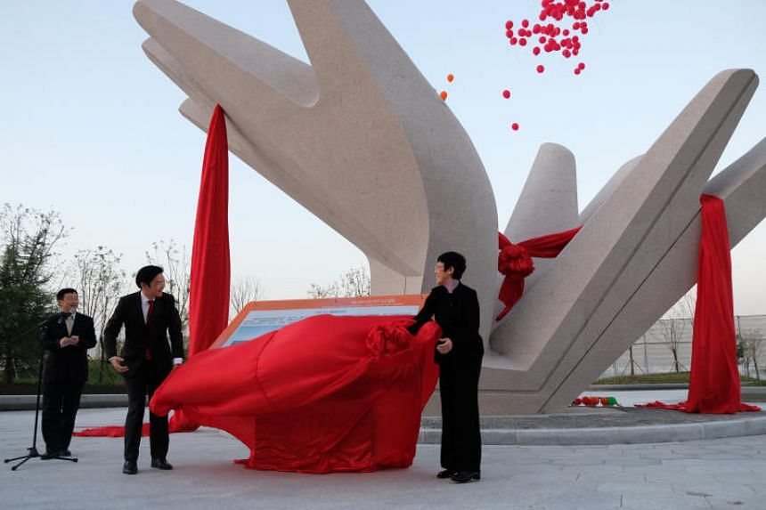 Minister for National Development Lawrence Wong (left) and China's vice minister for Housing and Urban-Rural Development Huang Yan unveiled a sculpture outside the China-Singapore Friendship Library, to commemorate the Tianjin Eco-city's 10th year an