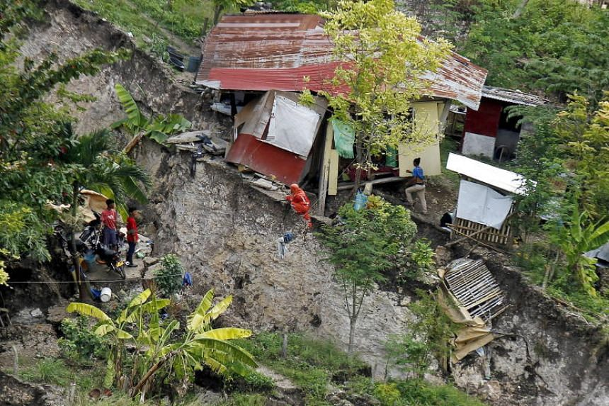 Filipino villagers and rescuers inspect a damaged home after a landslide in Naga city, Cebu province, Philippines, on Sept 22, 2018.