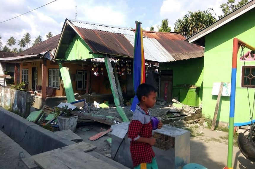 A boy walking in front of a collapsed house in Donggala after the quake.