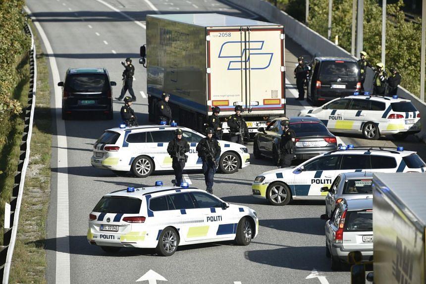 Police vehicles block the street leading to the Oeresund Bridge near Copenhagen, Denmark.