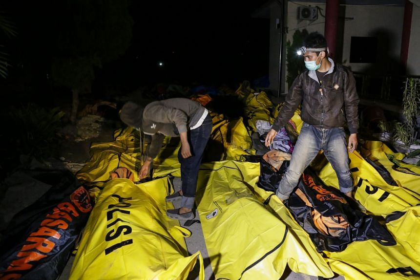 Indonesian men check victims' bodies as they look for their relatives at a police hospital in Palu, Central Sulawesi.