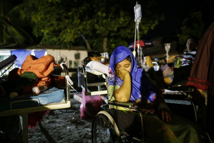 An Indonesian earthquake survivor rests as she gets medical treatment outside a military hospital in Palu.