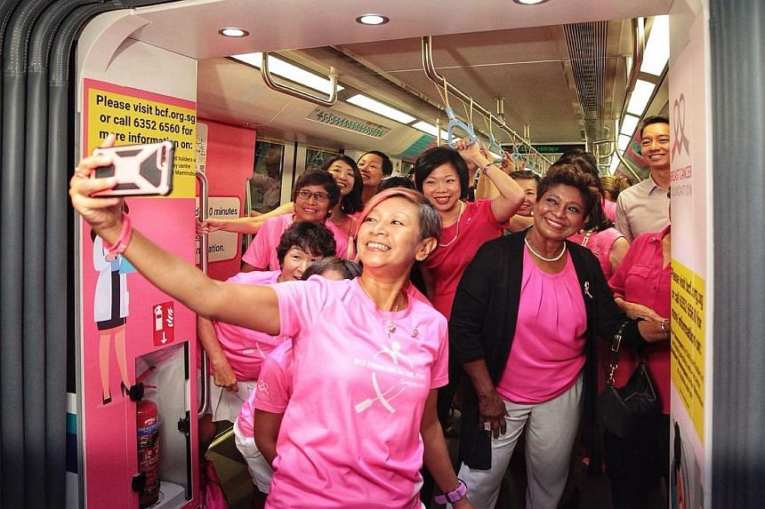 Breast Cancer Foundation's (BCF) Paddlers in Pink dragon-boat members, with Senior Minister of State Sim Ann (centre) and BCF president Noor Quek (in black cardigan), taking a wefie at the launch of the Pink Train yesterday. The train features the me