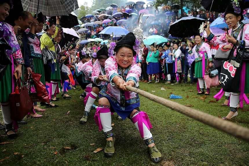 """Ethnic Miao women taking part in a tug of war on Thursday to celebrate a local festival in the Rongshui Miao autonomous county of southern China's Guangxi Zhuang autonomous region. The festival, known as """"Bohui"""", takes place twice a year on a mountai"""