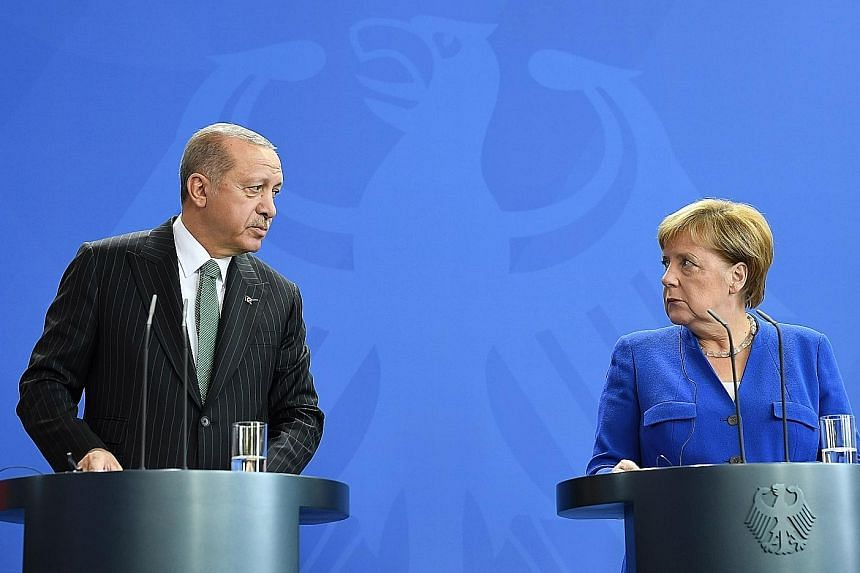 Turkish President Recep Tayyip Erdogan and German Chancellor Angela Merkel speaking at a news conference in Germany yesterday. Mr Erdogan is on a state visit to patch bilateral ties, but rights campaigners and German politicians are angered by the re