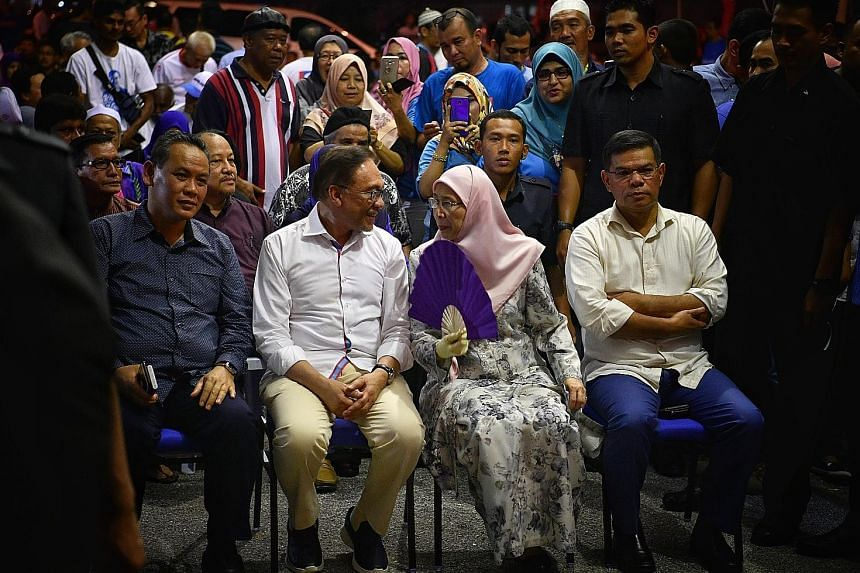 Datuk Seri Anwar Ibrahim with his wife, Deputy Prime Minister Wan Azizah Wan Ismail, and Parti Keadilan Rakyat officials at the party's election centre in Port Dickson. Mr Mohd Saiful Bukhari Azlan, a former aide to Mr Anwar who had accused him of so