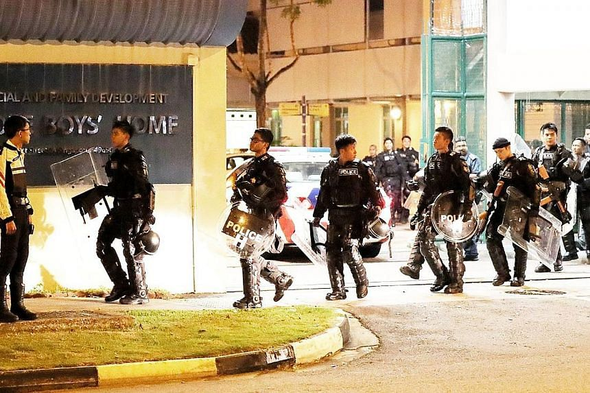 A strong police presence (left) was visible outside the Singapore Boys' Home in Jurong yesterday evening, with more than 15 police vehicles and 10 police bikes spotted there around 7pm. At about 8pm, officers in riot gear (below) were seen leaving th