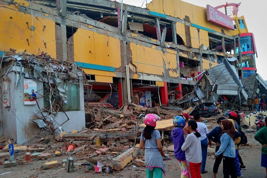 Residents stand in front of a damaged shopping mall after an earthquake hit Palu, Sulawesi Island, on Sept 29, 2018.