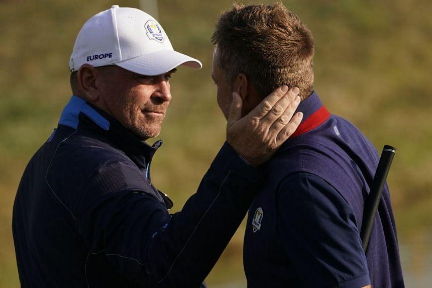 Europe's Danish captain Thomas Bjorn (left) congratulates Europe's Swedish golfer Henrick Stenson after he won his foursomes match.
