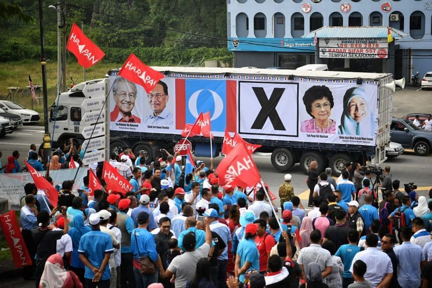 Supporters of Pakatan Harapan waving flags in front of a bus with a banner of the party's leaders.