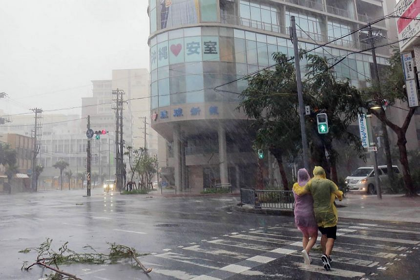 A couple crosses the street in heavy rain in the city centre of Naha, Okinawa prefecture, on Sept 29, 2018.