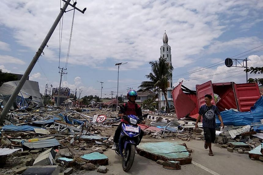Residents making their way along a street full of debris after an earthquake and tsunami hit Palu, Sulawesi island, on Sept 29, 2018.