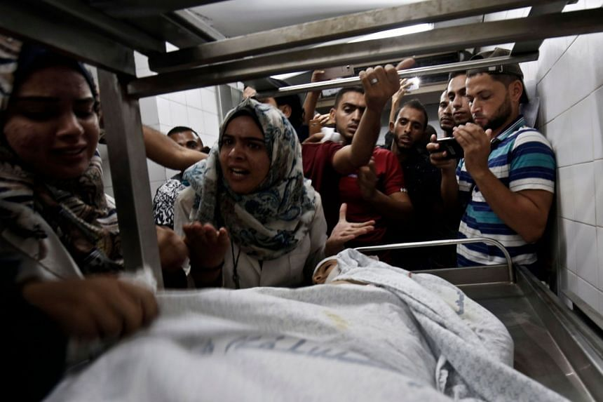 Relatives of Palestinian Nasser Mosabih, 12, mourn over his body at a hospital in Khan Yunis in the southern Gaza Strip.