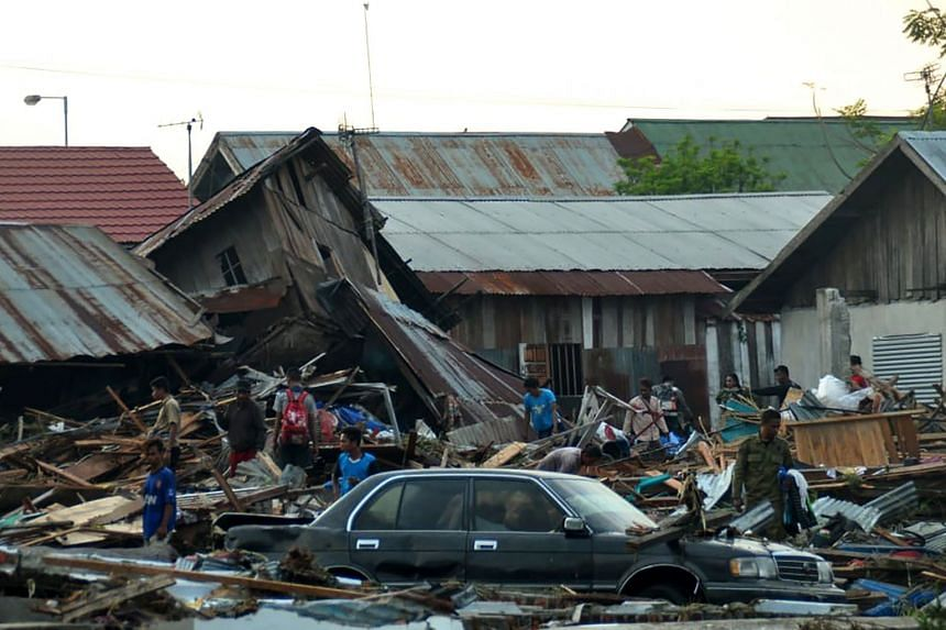 Residents trying to salvage belongings from their homes which collapsed after an earthquake and tsunami hit Palu.