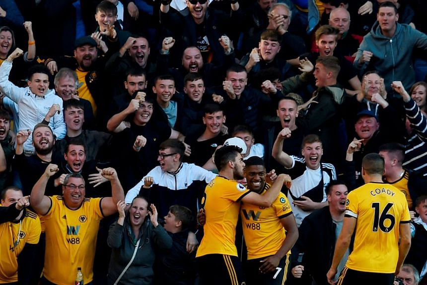 Cavaleiro celebrates scoring Wolves' first goal with Ruben Neves and Conor Coady.