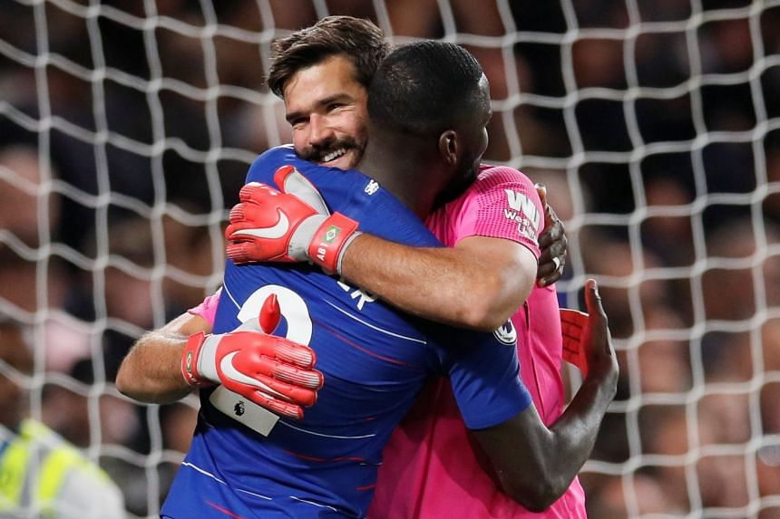 Chelsea's Antonio Rudiger embraces Liverpool's Alisson after the match.