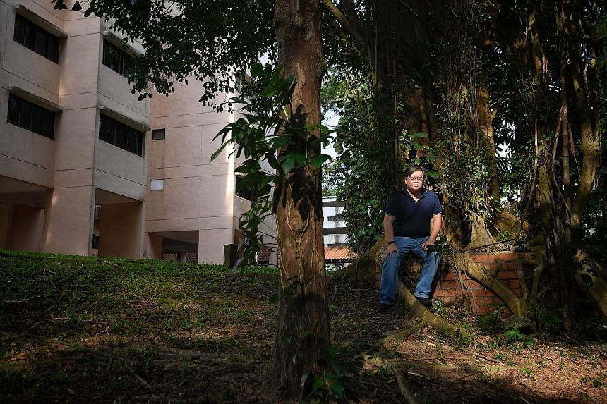Left: Dr John Kwok, a research fellow at the S. Rajaratnam School of International Studies, at one of the shafts. Above: A Ficus tree growing over what appears to be a well or an underground shaft at Normanton Park.