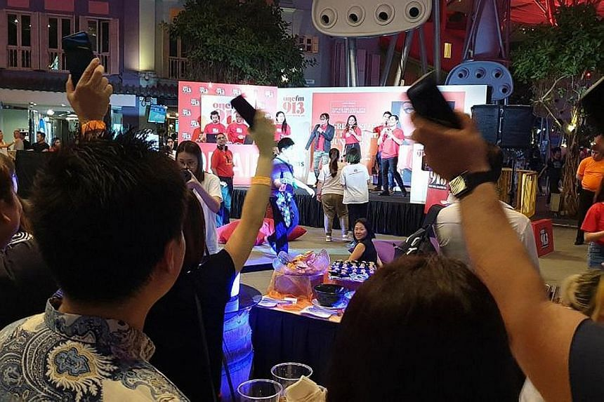 Fans joining the One FM 91.3 crew in counting down to the No. 1 song at Clarke Quay Fountain Square last Friday.