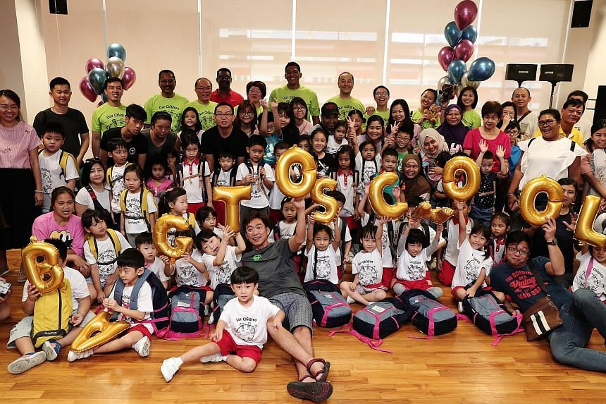 Ang Mo Kio GRC MP Darryl David (back row, centre, in green T-shirt) with grassroots volunteers, donors, parents and the kindergarten children entering Primary 1 next year. The children received school bags with new uniforms, shoes and socks for Ci Yu