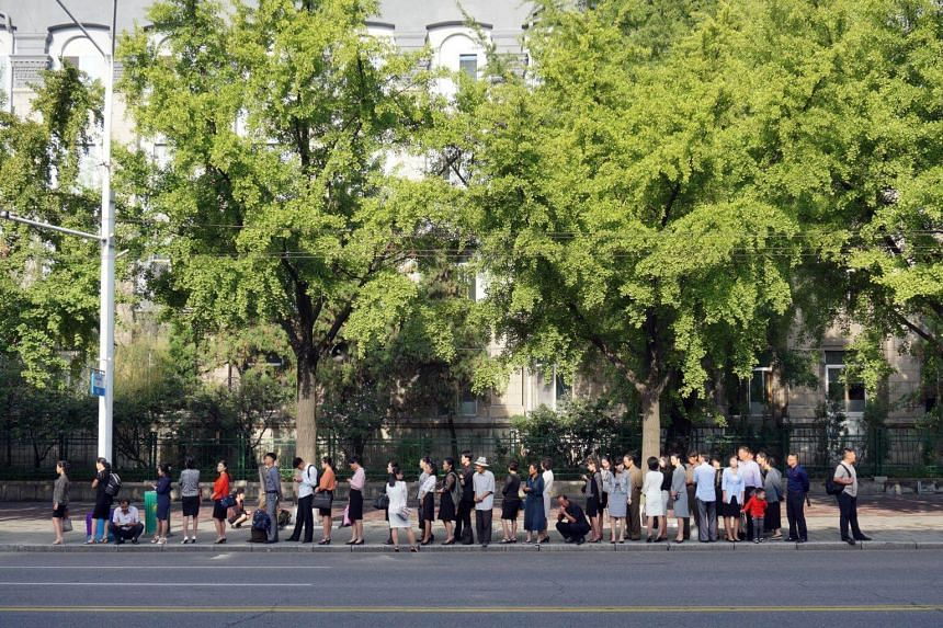 People waiting for public buses during morning rush-hour in Pyongyang.