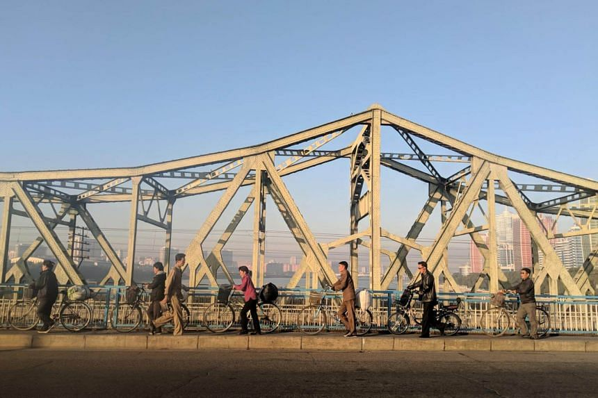Cyclists disembark and push their bicycles across a bridge that spans the Taedong River during the morning peak hour, on Sept 25, 2018.