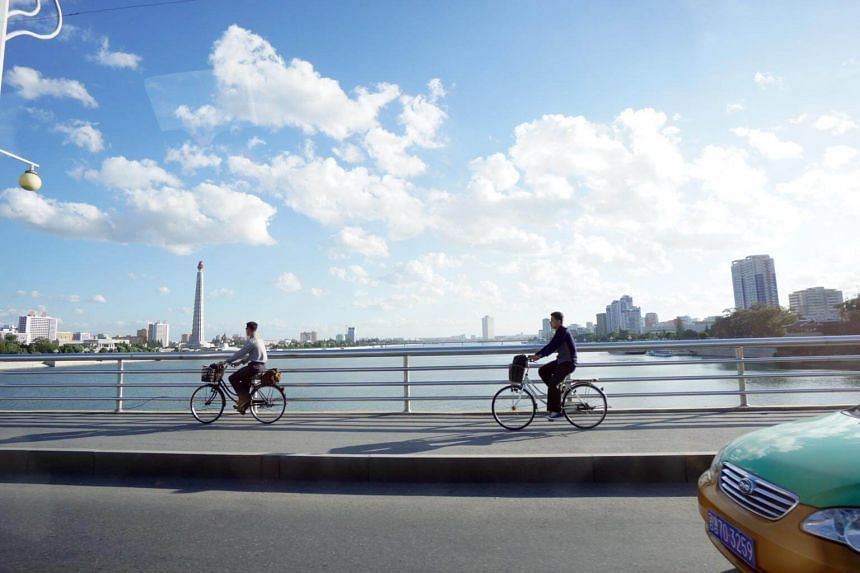 Two men cycle across a bridge that spans the Taedong River in Pyongyang, on Sept 23, 2018.