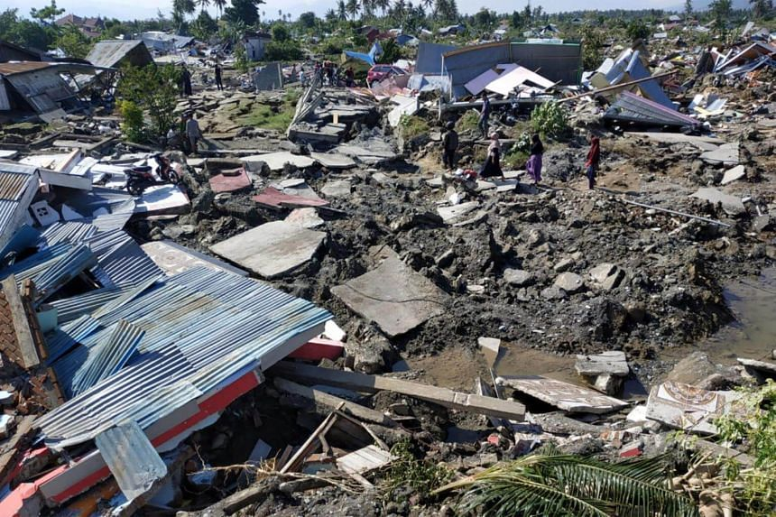 People walk through a residential area after an earthquake and tsunami in Palu, Central Sulawesi, Indonesia, on Sept 30, 2018.