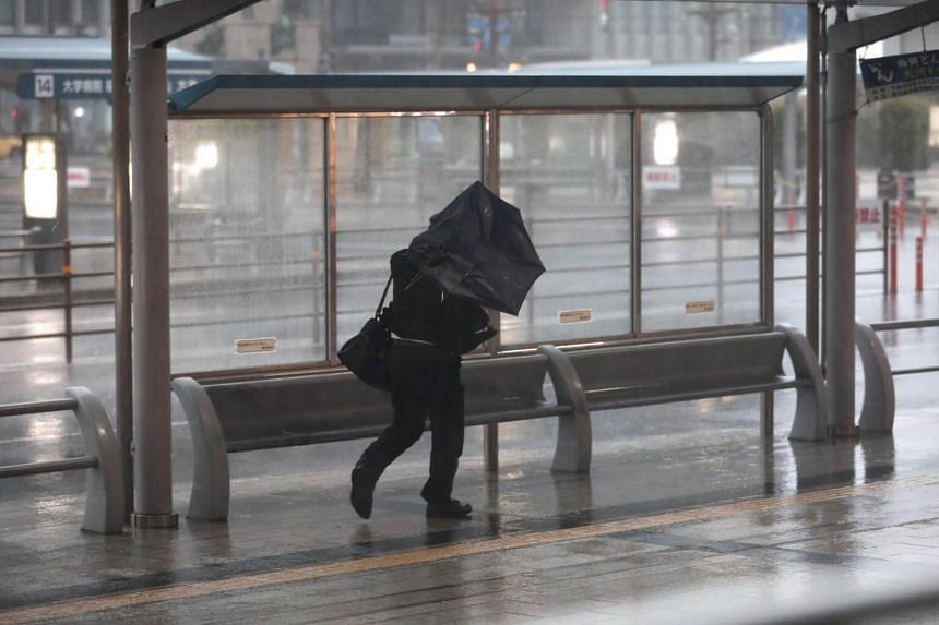A man struggles to hold his umbrella against strong wind and rain in Kagoshima, on Kyushu island, on Sept 30, 2018.