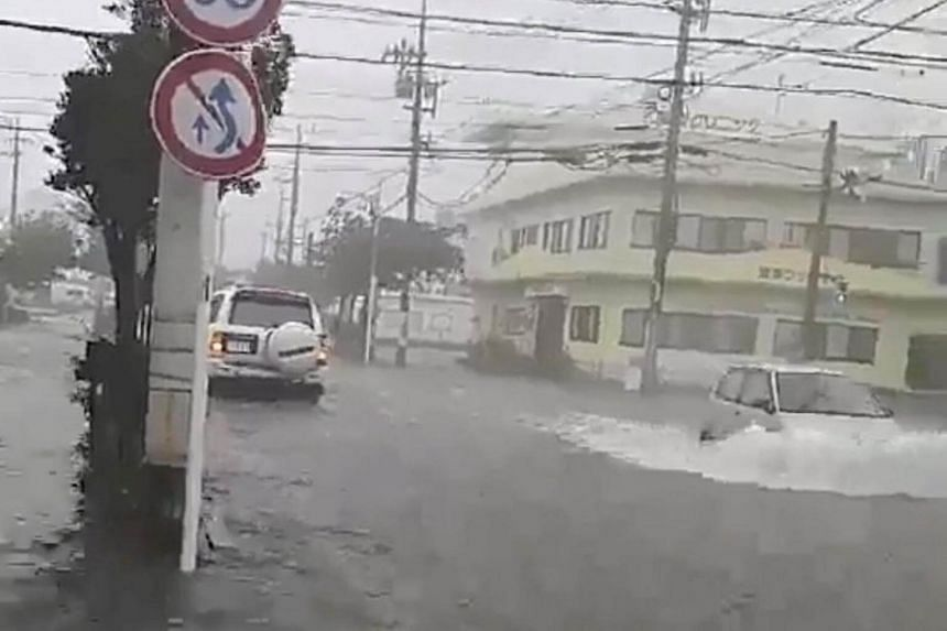 A flooded road is seen amid heavy rain and winds ahead of Typhoon Trami in Okinawa City, Okinawa Prefecture, in this still frame taken from social media dated Sept 29, 2018.