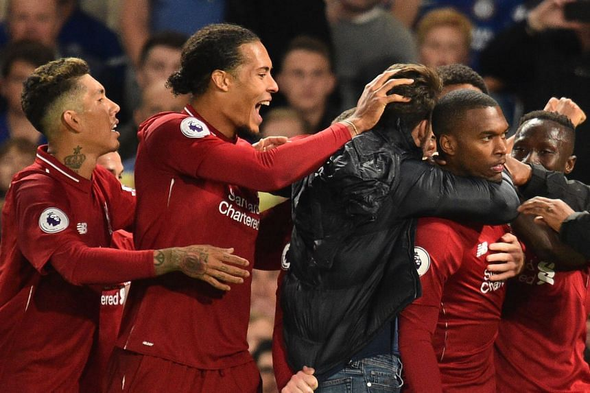 Liverpool's English striker Daniel Sturridge (right) celebrates with team mates after scoring.