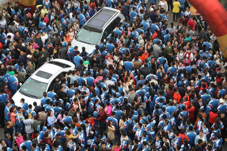 """Chinese students gather and wait to be taken to the venue for the annual national college entrance examination, or """"gaokao"""", while their parents see them off in Dandong on June 5, 2018."""