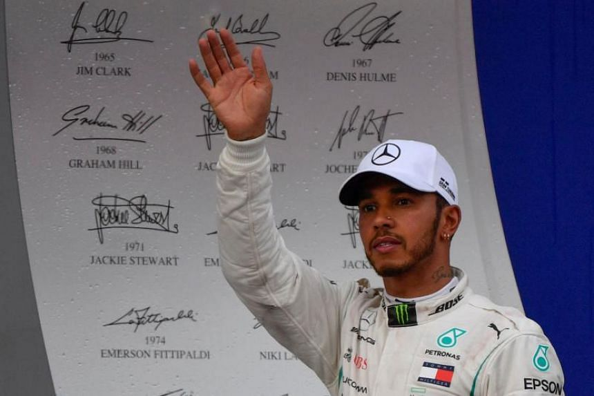 Mercedes' British driver Lewis Hamilton celebrates during the podium ceremony for the Formula One Russian Grand Prix at the Sochi Autodrom circuit in Sochi, on Sept 30, 2018.