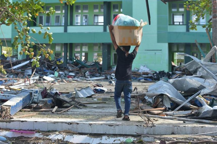 A man carries away looted goods from Palu Grand Mall on Sept 30, 2018, after an earthquake and a tsunami struck the area in Indonesia's Central Sulawesi province.