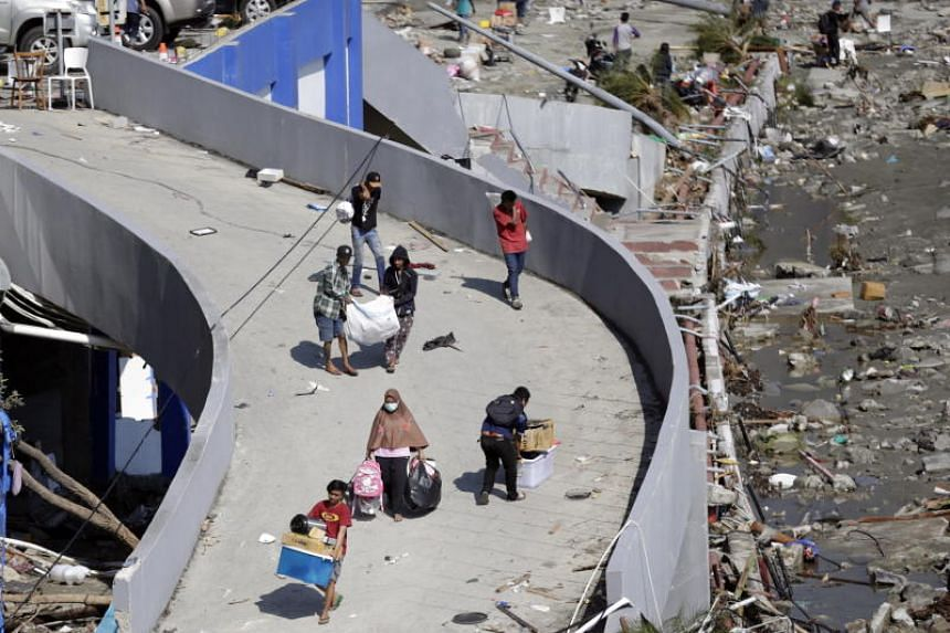 People carry goods looted from a tsunami-devastated shopping mall in Palu, Indonesia, on Sept 30, 2018.