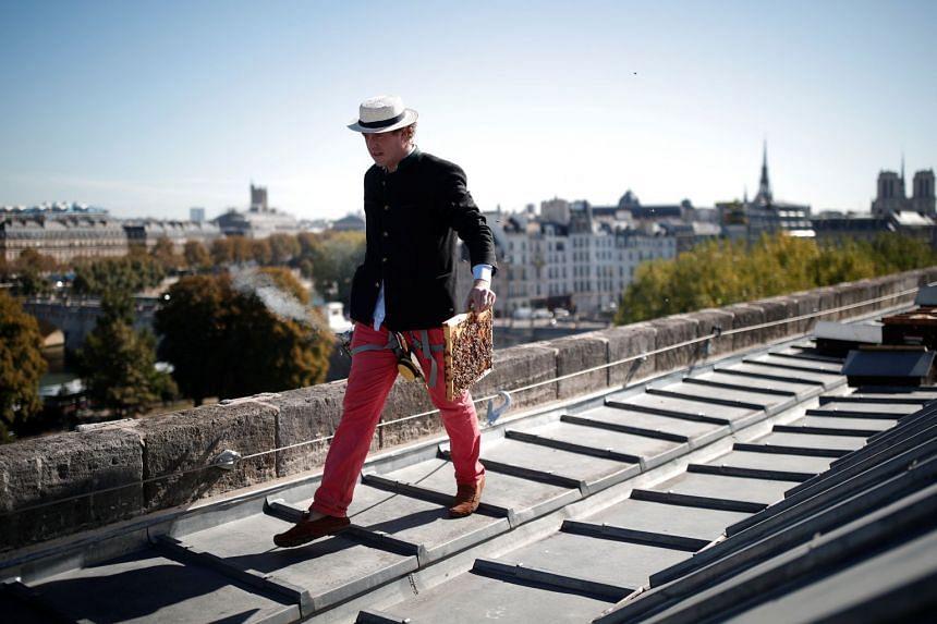 Beekeeper Audric de Campeau walks on the rooftop of the Monnaie de Paris in Paris, France.