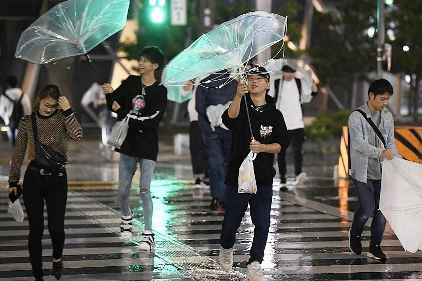 Pedestrians struggling against the strong winds and rain caused by Typhoon Trami in the city of Nagoya in central Japan yesterday.