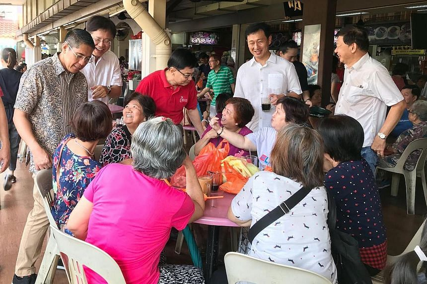 (Standing, from far left) Senior Minister of State Maliki Osman, Ang Mo Kio GRC MP Gan Thiam Poh, Finance Minister Heng Swee Keat and Education Minister Ong Ye Kung talking to residents at Hougang Village, which is part of Sengkang South division, du