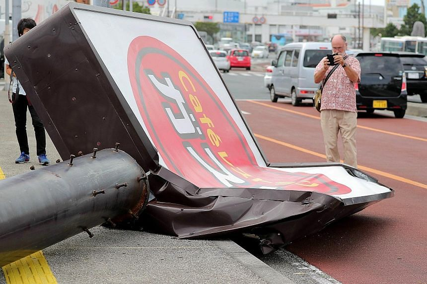 A collapsed restaurant signboard in the city of Urasoe on the southern island of Okinawa. Nearly 500,000 households in the south-western region of Kyushu and Okinawa have lost power after Typhoon Trami hit the area.