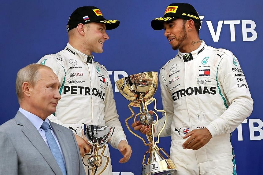 Lewis Hamilton with teammate Valtteri Bottas after getting him onto the podium's top step, as Russian President Vladimir Putin watches.