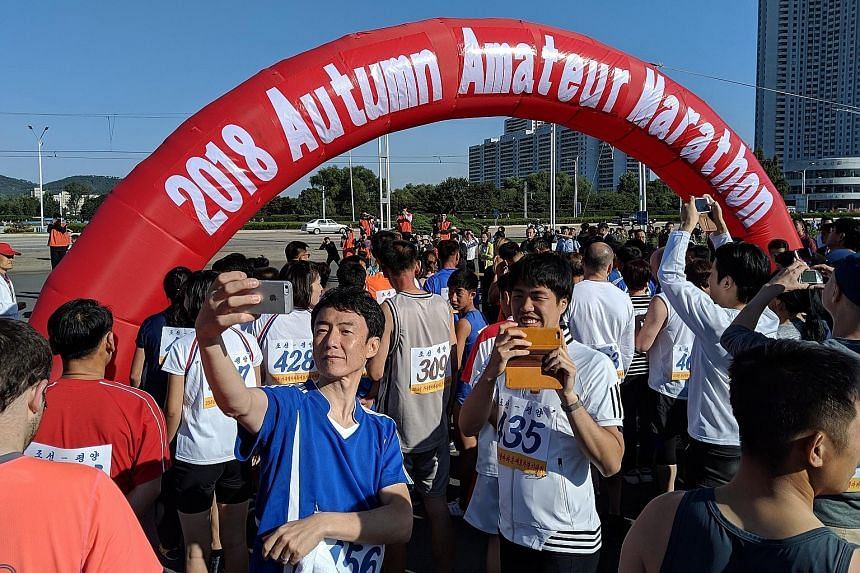 Runners taking selfies at the flag-off point of the Pyongyang Autumn Amateur Marathon on Sept 23. The run is geared at amateur runners amid burgeoning interest in long-distance running, said the organisers.