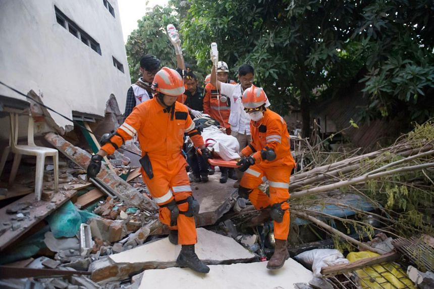 Rescue personnel evacuate an earthquake survivor from the rubble of a collapsed restaurant in Palu, Sulawesi, on Sept 30, 2018.