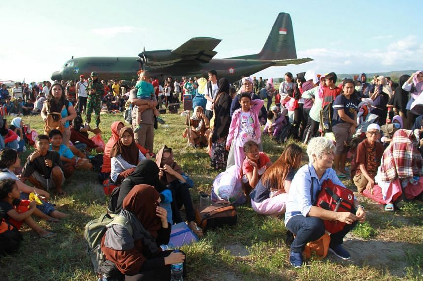 Local residents affected by the earthquake and tsunami wait to be airlifted by military planes at Mutiara Sis Al Jufri Airport in Palu, Sulawesi, on Sept 30, 2018.
