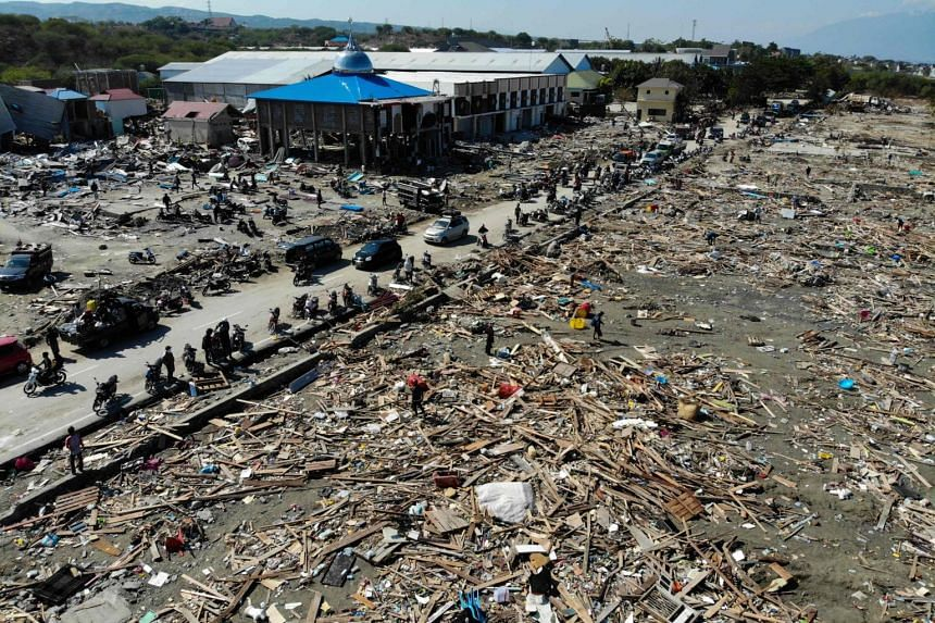 Earthquake survivors search for useable items among debris in Palu, on Oct 1, 2018.