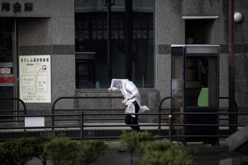 A pedestrian walks against a strong wind after Typhoon Trami hit the city of Kagoshima on Kyushu island, on Sept 30, 2018.