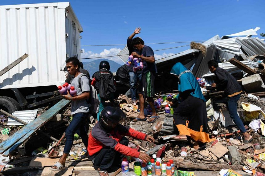 Indonesians salvaging usable items from the debris of a collapsed building in Palu, Central Sulawesi on Oct 1, 2018, after an earthquake and tsunami hit the area last Friday.