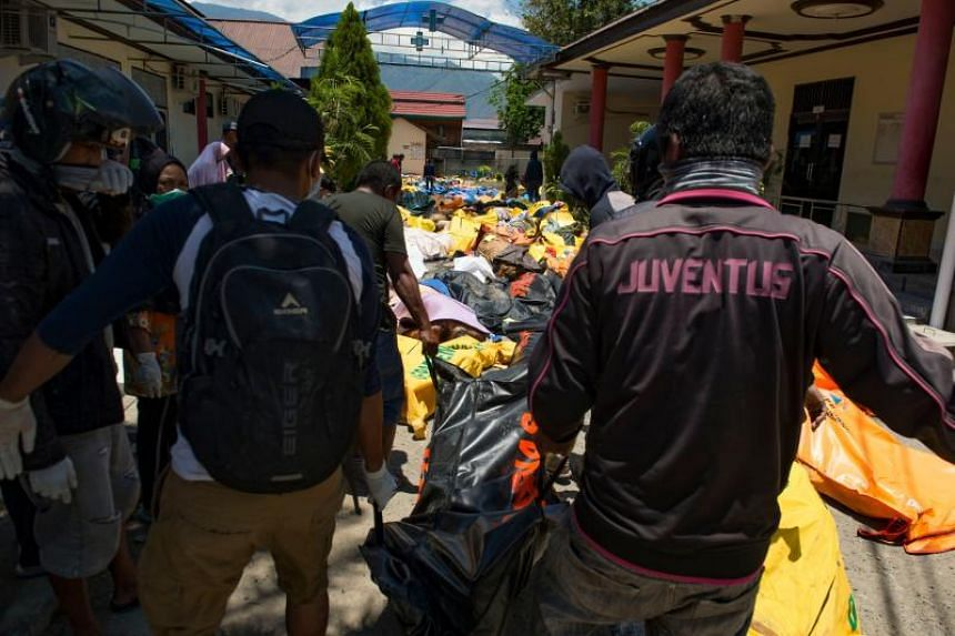 Rescue personnel carry the body of an earthquake victim to the compounds of a police hospital in Palu, Indonesia's Central Sulawesi, on Sept 30, 2018, following a strong earthquake in the area.