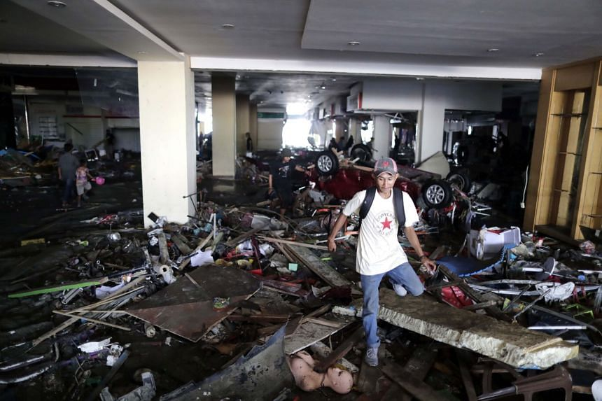A resident makes his way through debris inside a mall wrecked by a tsunami at Talise beach in Palu, Central Sulawesi.
