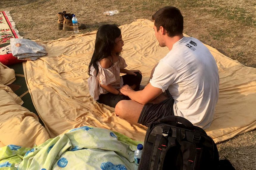 Belgian paraglider Francois de Neuville with the little girl he and Mr Ng rescued from the Mercure Hotel in Palu.