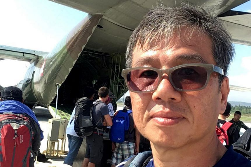 Singaporean paraglider Ng Kok Choong waiting to be evacuated on Saturday at Palu airport, where the air traffic control tower was toppled in the quake.