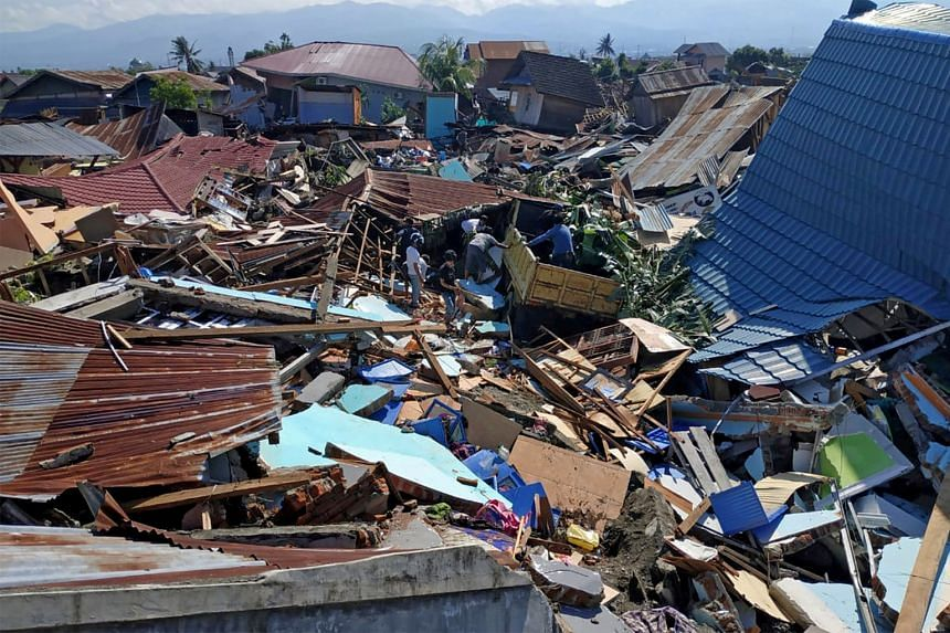 People searching among the debris in a residential area yesterday following Friday's earthquake and tsunami in the Indonesian city of Palu in Central Sulawesi. The disaster management agency said 16,700 people have been displaced and about 2.4 millio